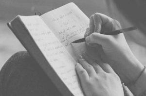 Personne écrivant sur un cahier
